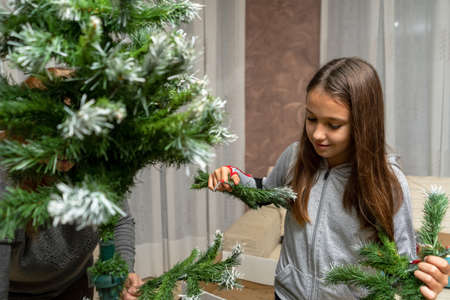 Pretty little girl assembling the Christmas tree in her living room. Illusion concept