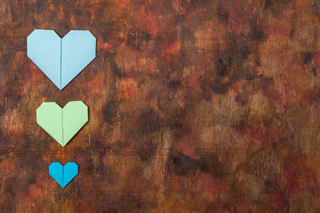 Origami hearts made with colored paper for congratulations on Valentine's Day for couples in love, on an old wooden background in brown tones. Love concept