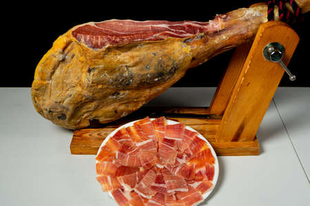 Detail of ham placed in a wooden ham holder ready to be cut. Exquisite food. Spanish tradition. Feeding concept