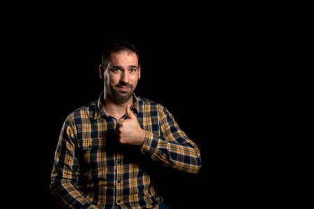 Attractive bearded man in a yellow plaid shirt posing isolated on black background. Fashion concept