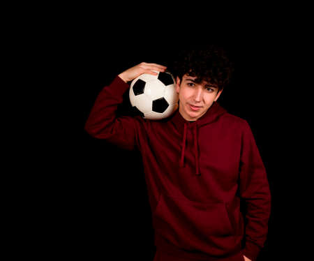 Attractive young man with a soccer ball posing on a black studio background. Sport concept