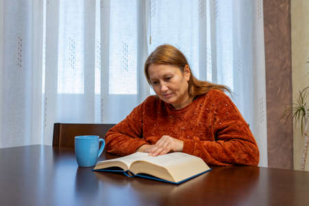 Pretty adult woman having a cup of coffee while reading a book sitting at the table in her living room. Home concept. Selective focus