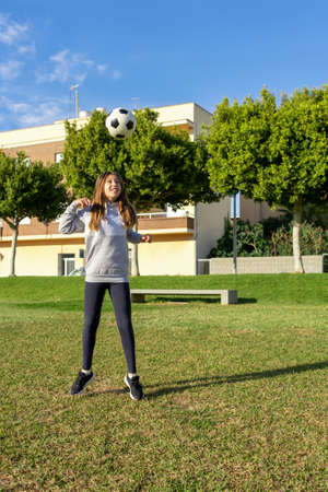 Beautiful little girl playing soccer in a nice park with natural grass on a sunny winter day. Exercise and healthy life concept