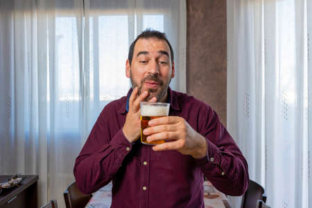 Attractive smiling bearded man in a purple shirt licking a fresh beer. Fun concept