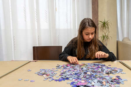 Pretty little girl in a black sweatshirt doing a puzzle in her living room. Entertainment concept