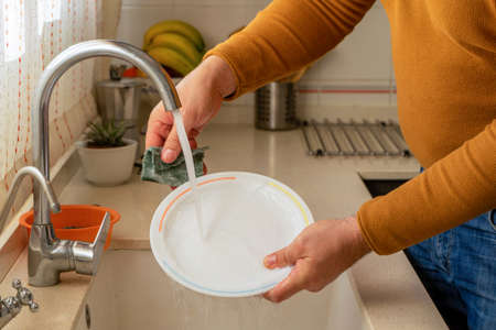 Detail of man's hands scrubbing a plate with a green scouring pad in the kitchen at home. Housework concept