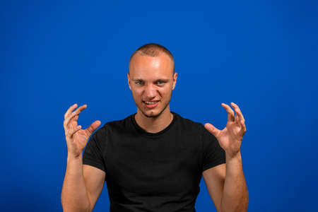 Evil young man with claw hands pissed off executing an evil plan isolated on blue studio background. Malice concept