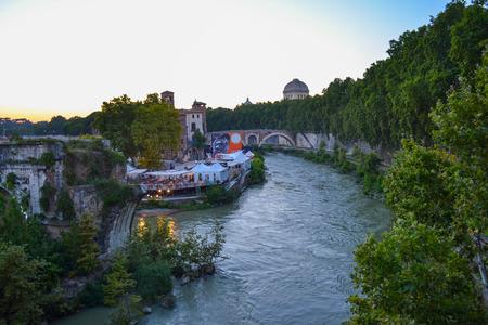 View of Pons Fabricius, Tiber Island and Tiber river from Ponte Palatino, in Rome, Italy, with San Gregorio della Divina Pieta at background. View of Fabricius Bridge or Ponte dei Quattro Capi from English Bridge.