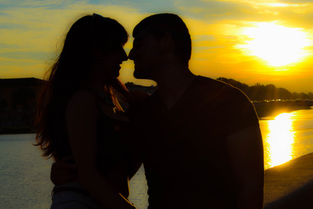 Silhouette of a romantic young couple kissing with blurred sunset and sea background