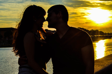 Silhouette of a romantic young couple kissing with sunset and sea background. Emotional photo Imagens