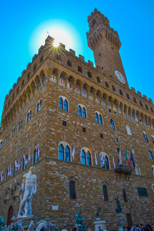 Vertical photo of Palazzo Vecchio (Old Palace) with Fountain of Neptune (Fontana del Nettuno) and David by Michelangelo at foreground, in Piazza della Signoria. Florence, Italy. Editorial
