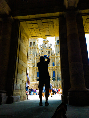 Dark silhouette of a photographer taking a picture of the Cathedral of Santiago de Compostela. Camino de Santiago