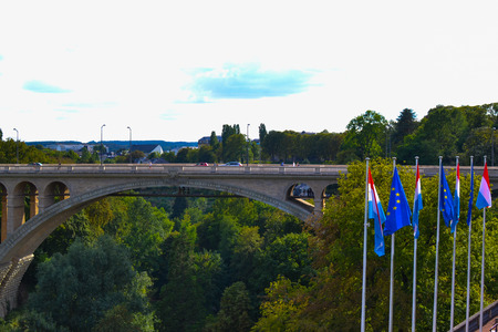 Adolphe Bridge (Pont Adolphe) in Luxembourg City, Luxembourg, with green trees and flags of Luxembourg and Europe at the foreground Stockfoto