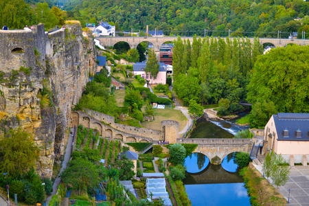View of Alzette river crossing the old town of Luxembourg City, Luxembourg, with a bridge and houses in one side and the wall in the other side
