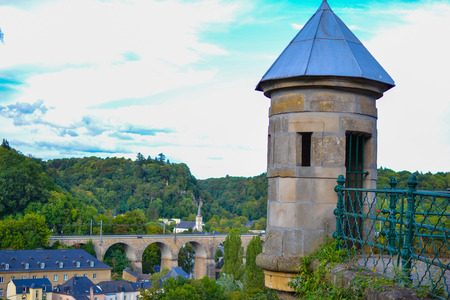 Tower of the wall of old town of Luxembourg City, Luxembourg, with a bridge with archs, houses and cliff at the background
