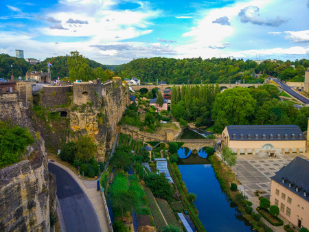 View of the Alzette river in the old town of Luxembourg City, Luxembourg, with St. John Church (church of St. John or St. Jean du Grund) in one side and the wall in other side