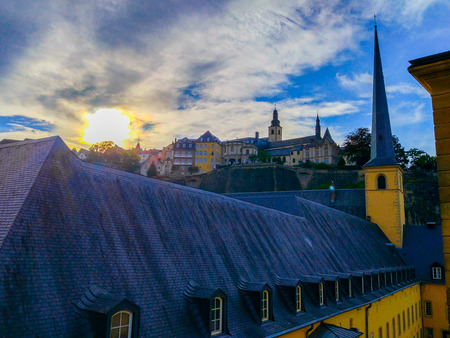 Sunset over St. John Church (church of St. John or St. Jean du Grund) in the Grund district, in the old town of Luxembourg, Europe, with Saint Michael's Church (Eglise Saint-Michel) at the background