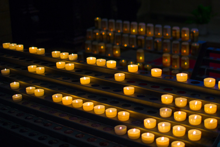 Many burning candles in a row with shallow depth of field Stock Photo