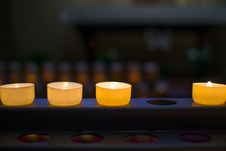 Close up of three burning candles in a row without one candle, with shallow depth of field. Incomplete.