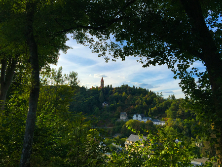View of Clervaux and the mountain and forest between two trees.