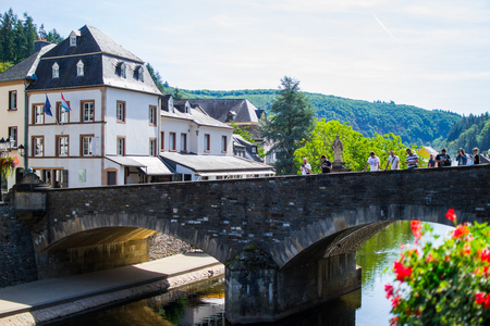 View of the Our river with a stone bridge in the old town of Vianden, Luxembourg, with typical houses at the background