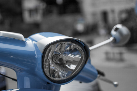 Close up of the headlight of a blue classic scooter with defocused background