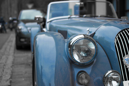 Close up of the headlight of a blue classic sport car, with blurred background