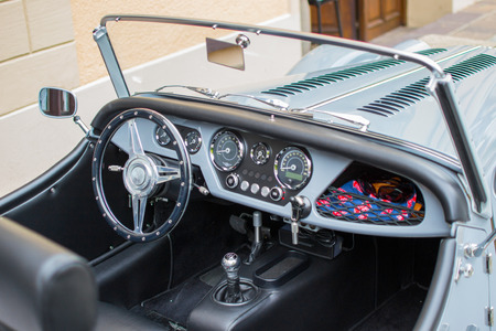 View of the interior of a classic convertible car, with a metallic steering wheel and the dashboard