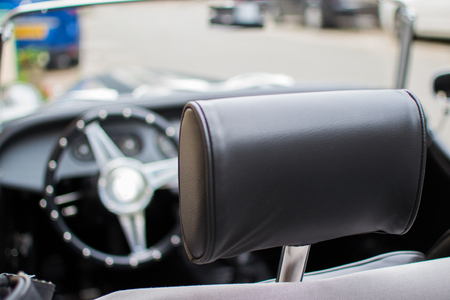 Close up of a leather headrest of a classic convertible car with the defocused steering wheel at the background