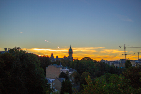 View of Musée de la Banque (Bank Museum) in Luxembourg City, Luxembourg, with green trees at the foreground and a beautiful sky with clouds and sunset Stock Photo