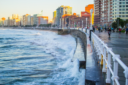 Waves splashing against the wall in San Lorenzo beach in Gijon, Asturias, Spain, with the promenade and buildings in one side