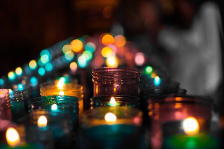 Close up of colorful candles in a dark spiritual scene. Commemoration, funeral, memorial. Religious symbolism. Stockfoto