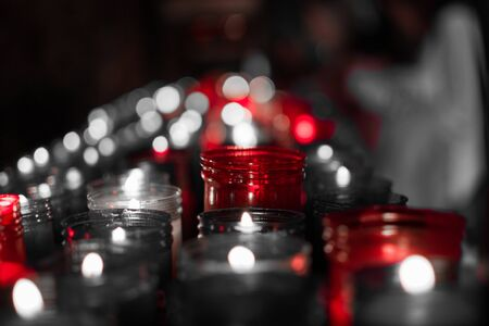 Desaturated red image of a closeup of colorful candles burning in the tunnel of Covadonga, Cangas de Onis, Asturias, Spain. Spirituality. Stock Photo