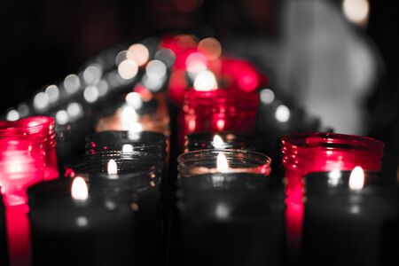 Closeup of colorful candles burning in the tunnel of Covadonga, Cangas de Onis, Asturias, Spain. Spirituality.