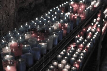 Desaturated closeup of colorful candles burning in the tunnel of Covadonga, Cangas de Onis, Asturias, Spain. Spirituality. Imagens