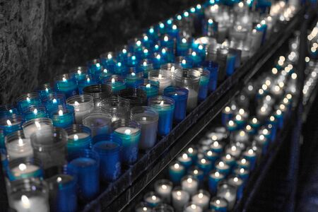 Desaturated blue image of a closeup of colorful candles burning in the tunnel of Covadonga, Cangas de Onis, Asturias, Spain. Spirituality.