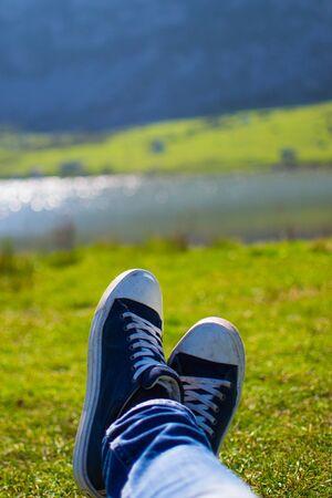 Gros plan vertical d'une paire de chaussures bleues et blanches relaxantes sur un pré vert avec un lac défocalisé en arrière-plan