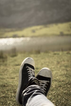 Vertical grunge picture of a close-up of a blue and white pair of shoes relaxing on a green meadow with a defocused lake in the background Banque d'images