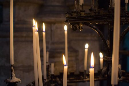 Close up of candles burning inside the Saint Bavo Cathedral (or Sint-Baafs Cathedral) in Ghent, Belgium, Europe. Spirituality.