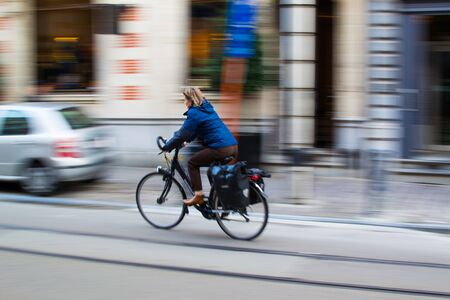 Ghent, Belgium; 10/31/2018: Panning effect photography of a woman riding on a bike through a street in the city