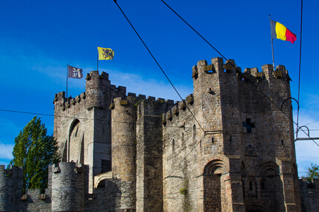 Gravensteen (or Castle of the Counts), famous medieval monument in Ghent, Belgium, with flags of Ghent, Flanders and Belgium on the top