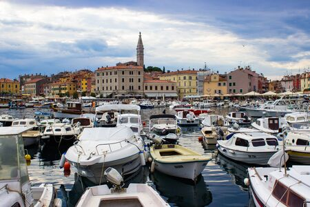 Rovinj, Croatia; 7/18/2019: Port of Rovinj with a lot of boats at the foreground and the old town and the tower of the Church of St. Euphemia at the background