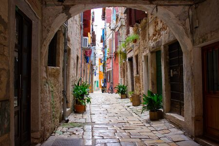 Picturesque arch with a colorful street at the background in the old town of Rovinj, Croatia