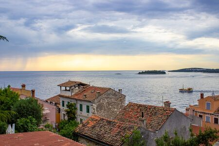 View of the Adriatic Sea with the roofs of the typical croatian houses and the green vegetation in the land, in Rovinj, Croatia