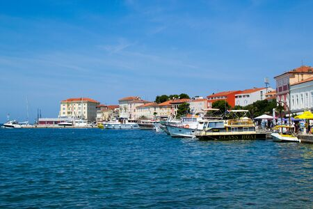 Porec (Parenzo), Croatia; 7/19/19: View of the typical croatian houses in the coastline of the old town of Porec (also called Parenzo), Croatia, with boats anchored on the port in Adriatic Sea