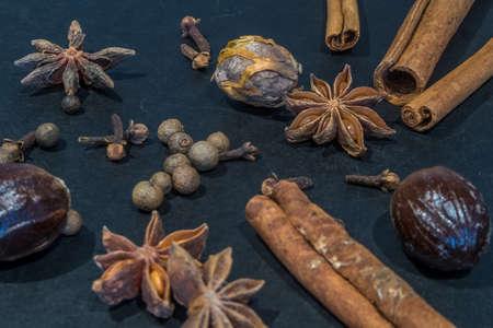 Assortment of seasonal spices arranged against a black background.  Includes Cinnamon Sticks, Allspice Berries, Nutmeg, Mace, Star Anise & Cloves