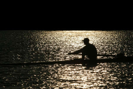 strenuous: Rowing alone at sunset Stock Photo
