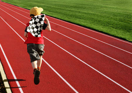 Boy with a checkered flag running on a racetrack