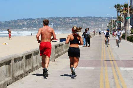 men exercising: Pareja corriendo a lo largo de la playa