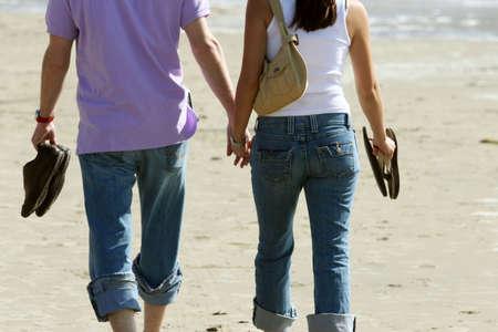 fema: Couple walking on the beach Stock Photo